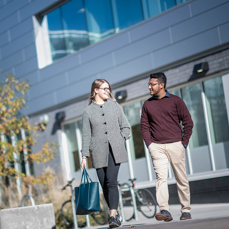 female and male students walking on campus